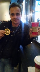 "Sebastian and his medal! The coffee, if you can read, was made for ""him"" .. I told the barista that it was for ""him"" when they asked for a name, and they went with it. Ha!"